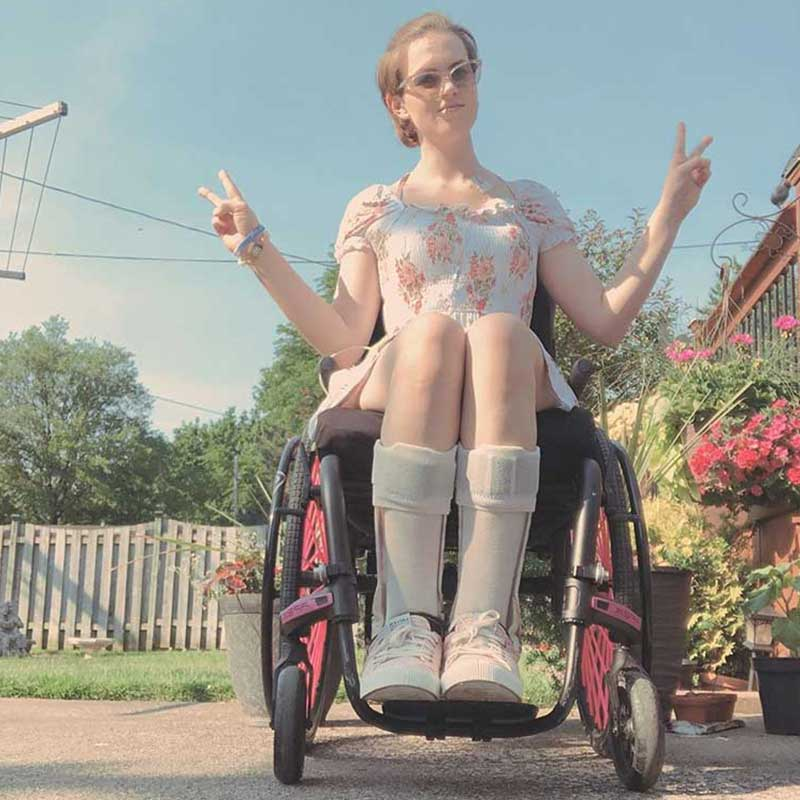 Woman in wheelchair showing peace sign and wearing medical alert bracelet