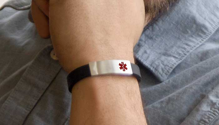 Man smiling and wearing silicone medical alert band