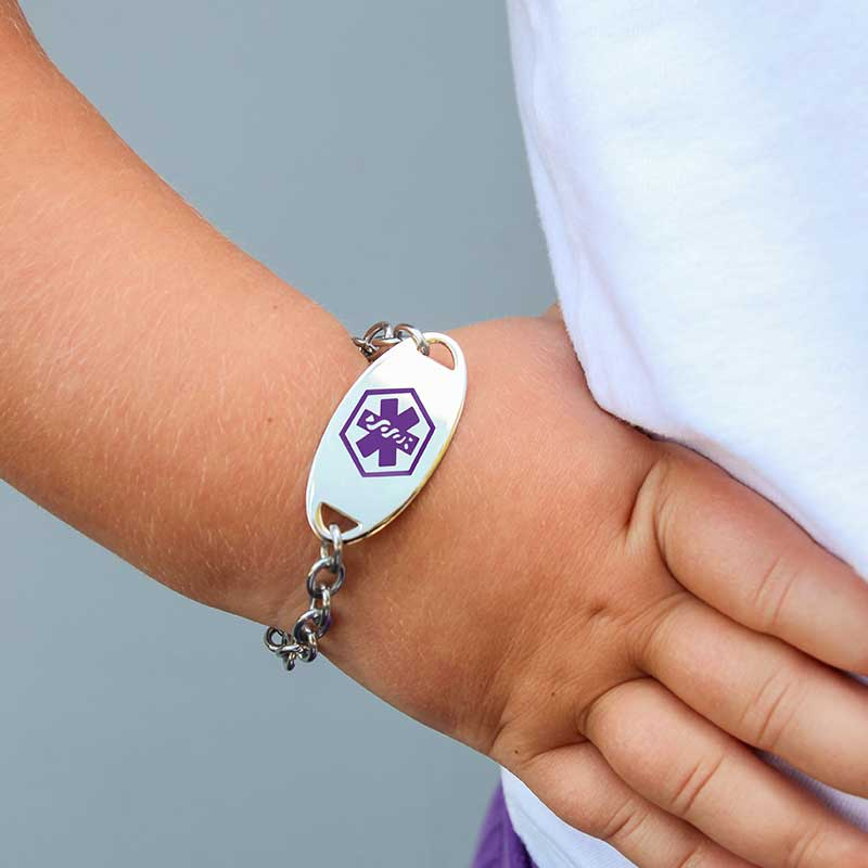 Young girl wearing medical alert tag with purple symbol