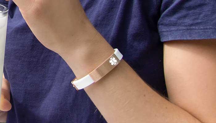 Girl wearing silicone and rose gold medical alert bracelet