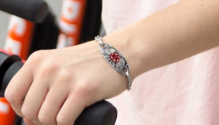 Girl holding handlebars wearing med alert with angel details