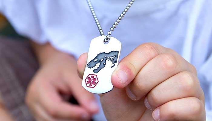 Boy showing medical alert dog tag with dinosaur design