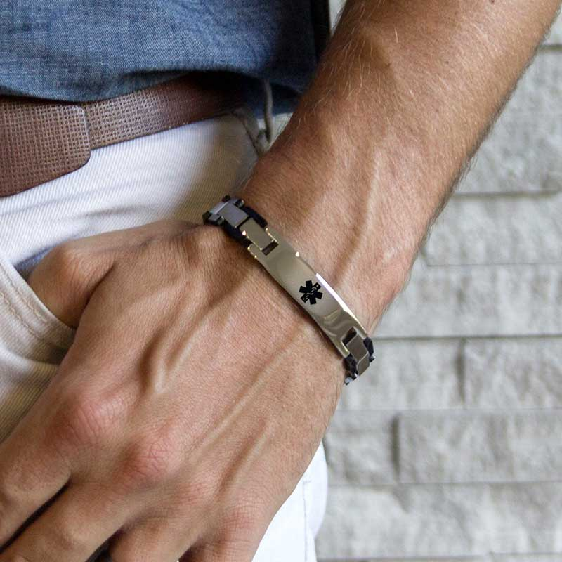 Man wearing silver linked medical alert bracelet with black accents
