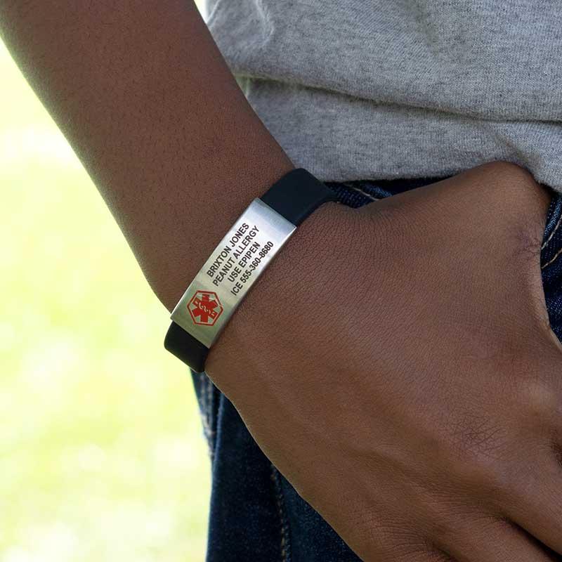 Man wearing silver linked medical alert bracelet with black accents