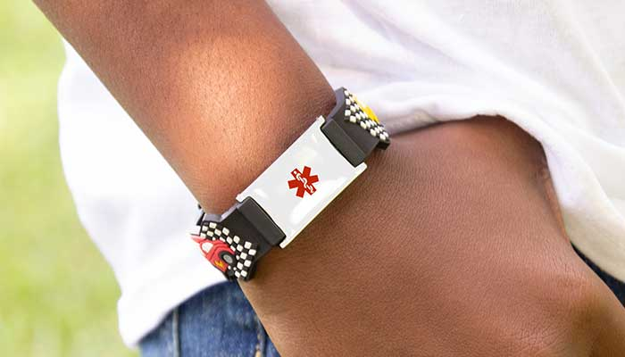 Boy wearing waterproof medical alert band with cars design