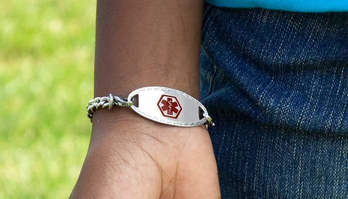 Boy wearing silver medical alert tag