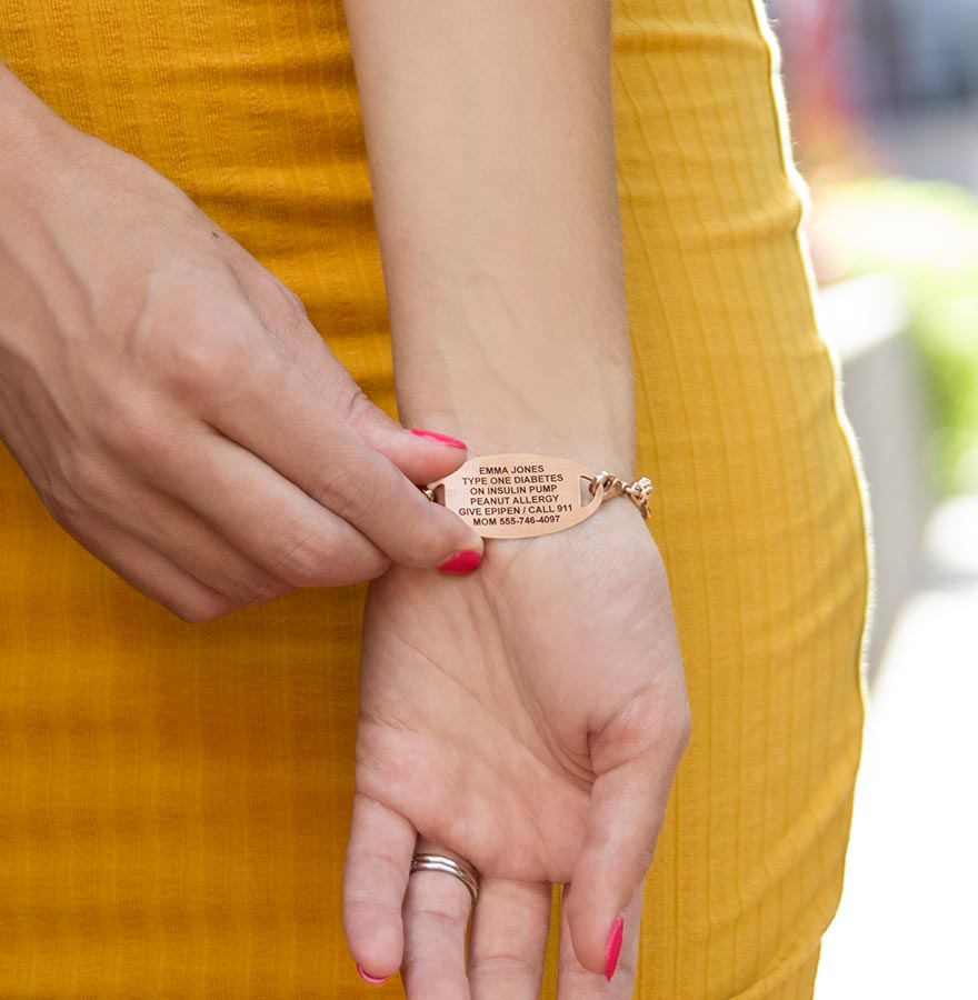 Woman in marigold yellow dress showing custom laser engraving on medical ID tag