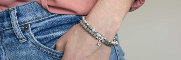 Lyla Stretch Medical ID Bracelet - woman in blush pink shirt and blue jeans wearing gray and silver crystal medical ID Bracelet