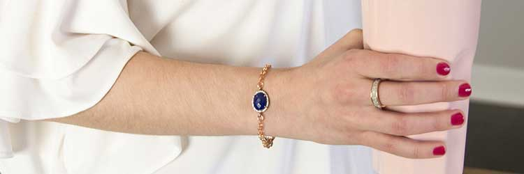 Morning Glory Medical ID Bracelet - women in white shirt holding light pink cup wearing rose gold chain medical ID bracelet with cobalt blue stone