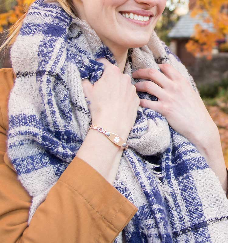 Woman wearing rose gold linked medical ID bracelet and scarf