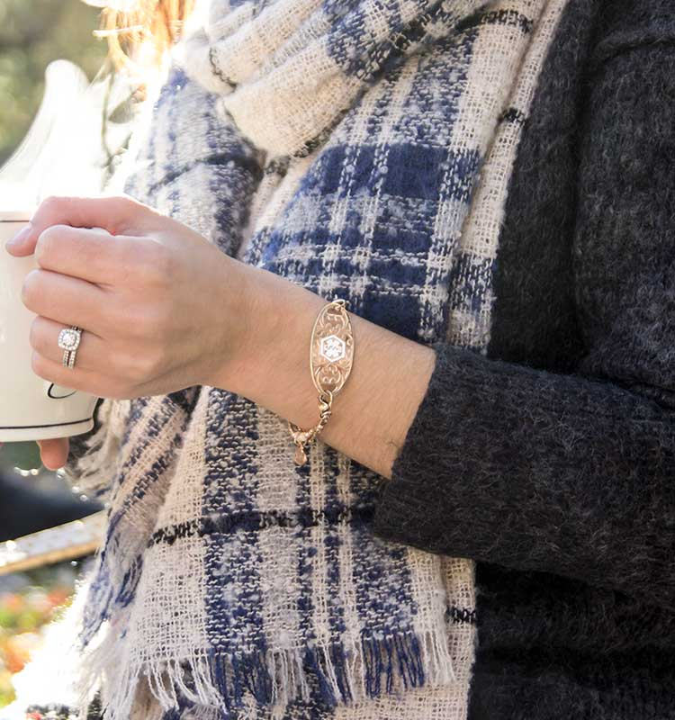 Woman wearing medical ID bracelet with decorative medical ID tag holding cup of tea