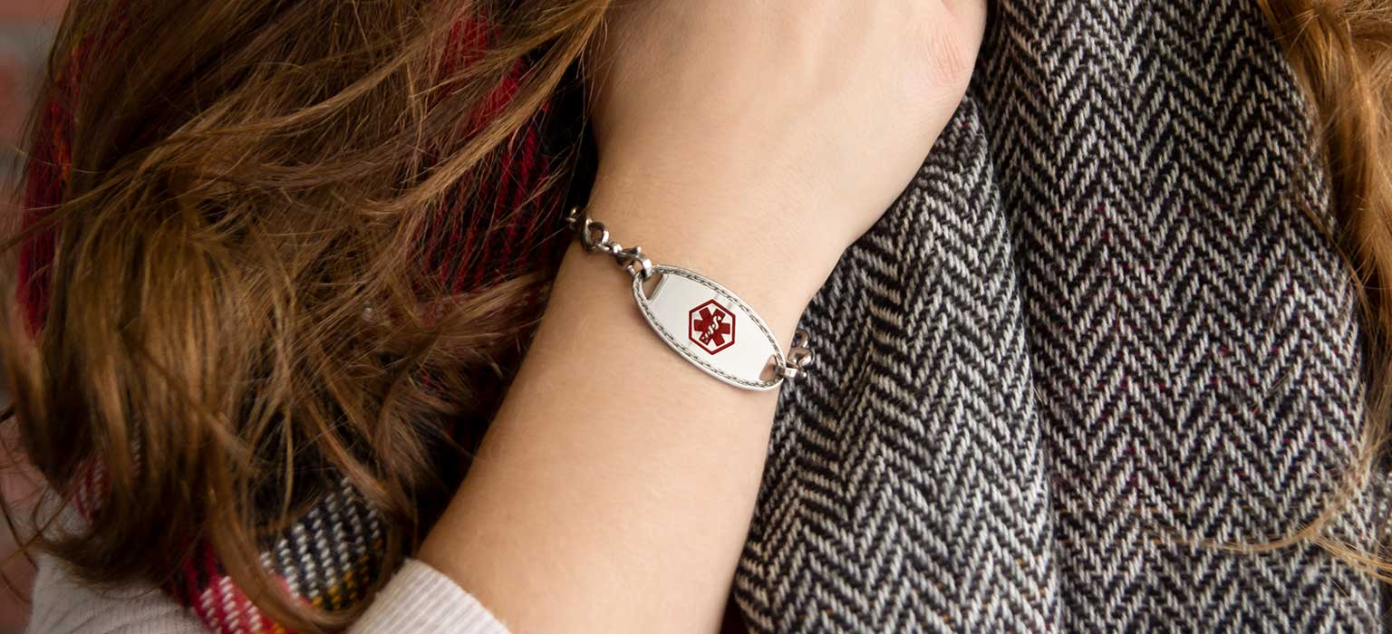 Women wearing medical ID bracelet with red medical caduceus symbol