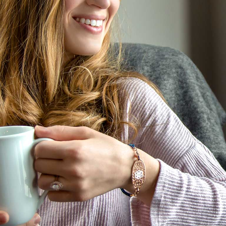Woman holding mug and wearing a rose gold medical ID tag