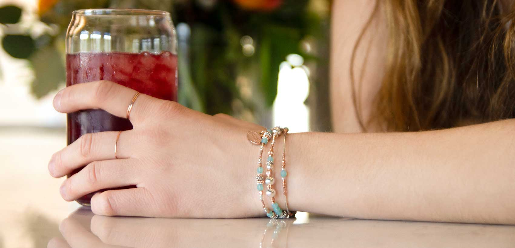 Woman wearing rose gold and blue beaded medical ID bracelet