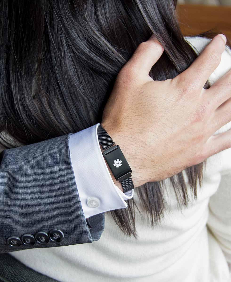 Man wearing black tone medical ID bracelet with mesh band and white caduceus symbol