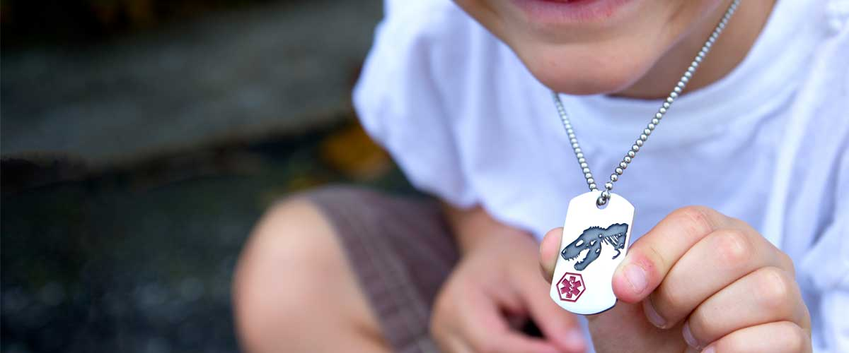 Boy holding medical ID dog tag necklace with dinosaur