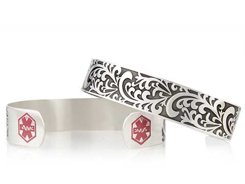Silver medical alert cuff with decorative inlay and red medical symbols