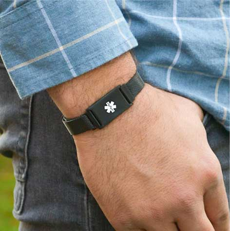 Man wearing blue shirt and black mesh medical alert bracelet band