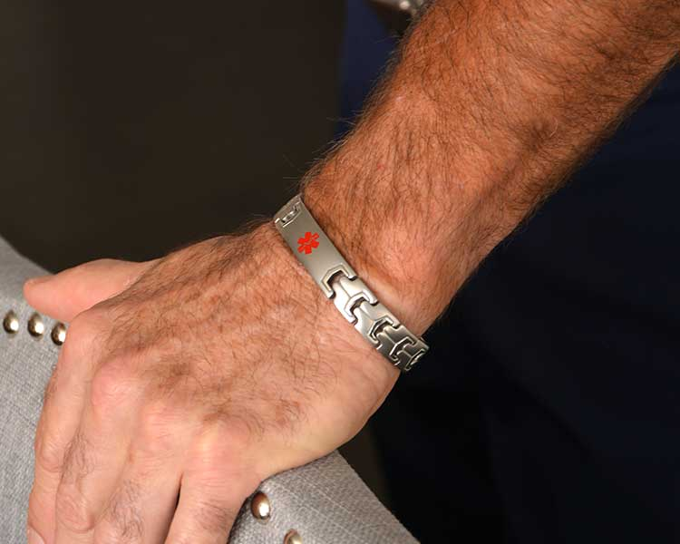 Man wearing silver tone medical alert bracelet with red medical symbol