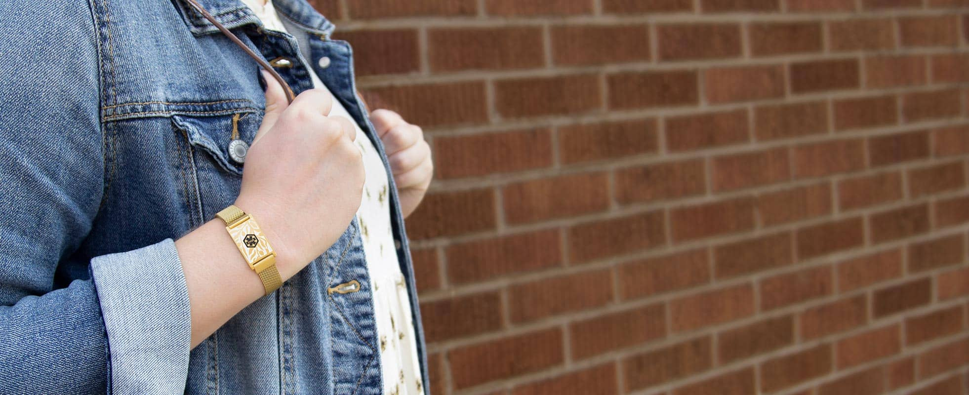 Woman wearing denim jacket and gold tone medical alert bracelet