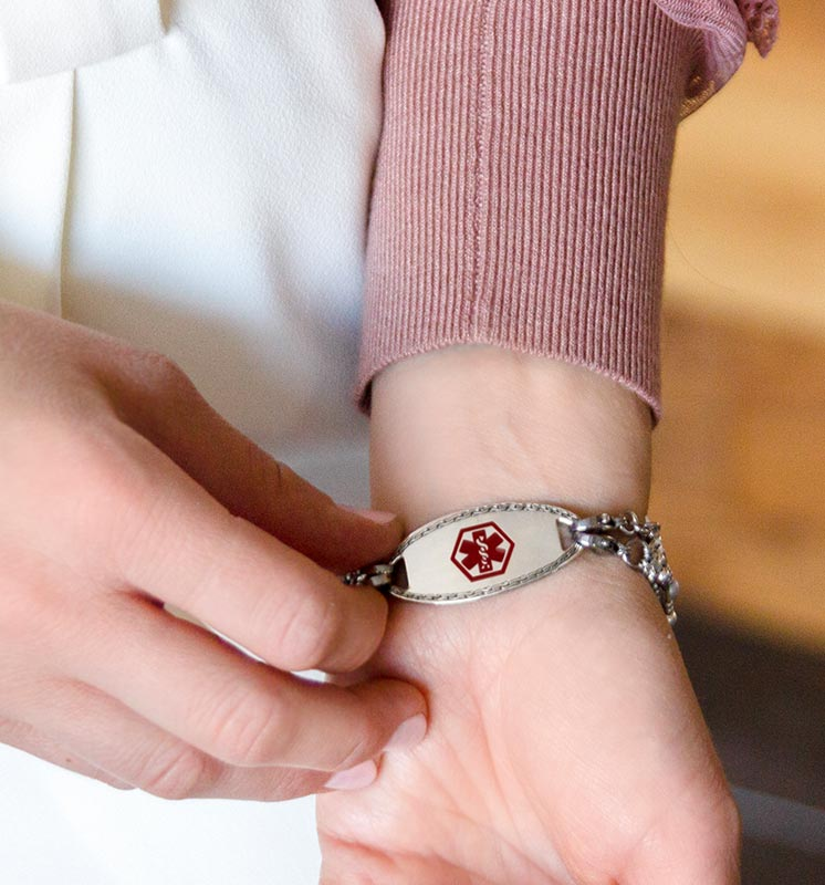 Woman showing silver tone medical alert tag with decorative border