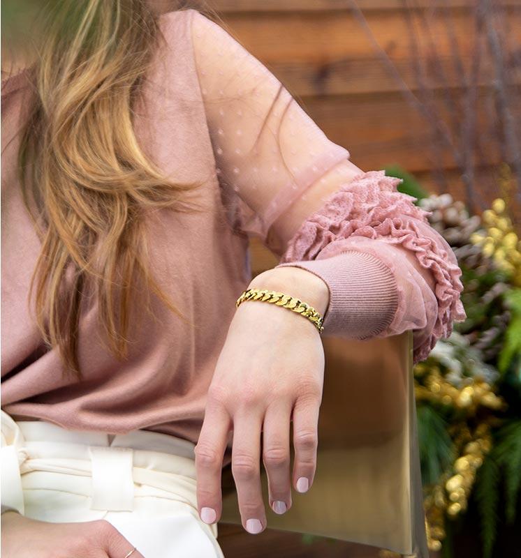 Woman in a pink shirt wearing a gold medical alert bracelet chain