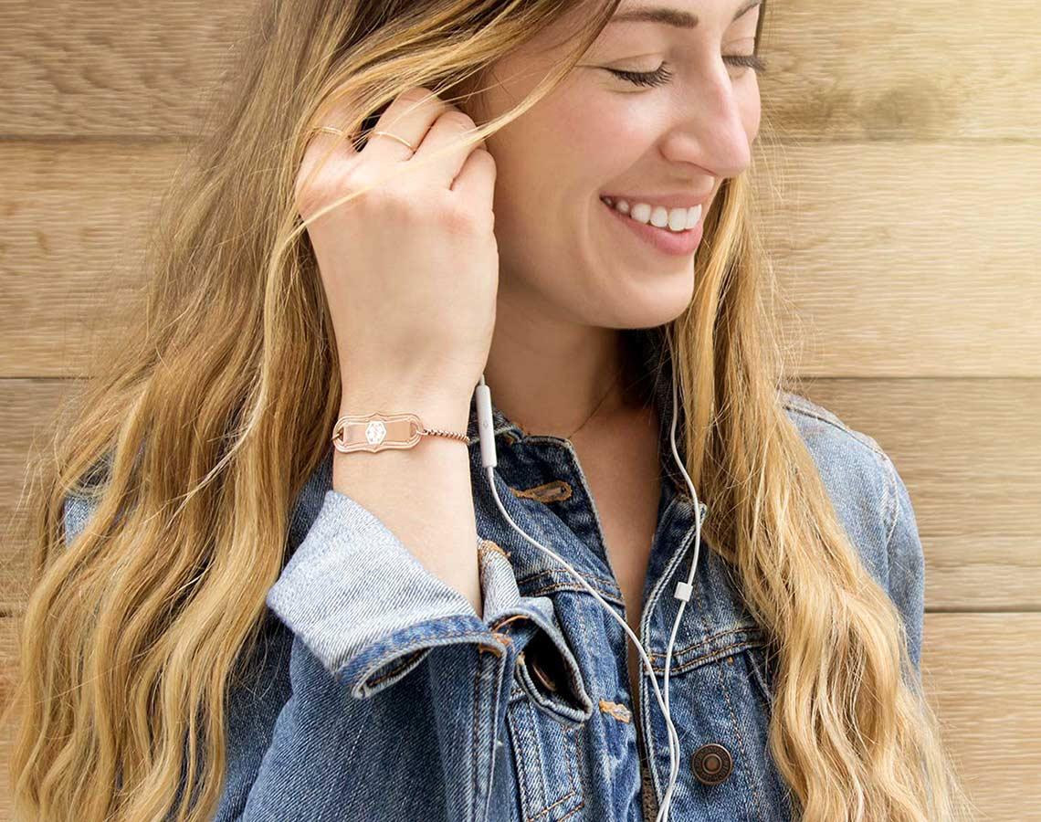 Smiling woman wearing jean jacket and rose gold medical alert bracelet