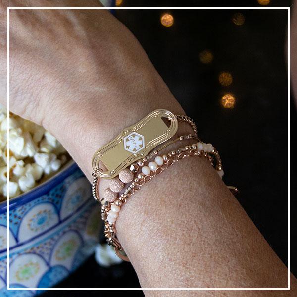 Hand reaching for popcorn wearing rose gold medical alert bracelet
