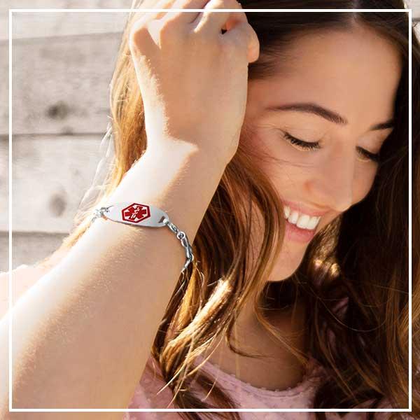 Smiling woman brushing hair back and wearing medical alert bracelet