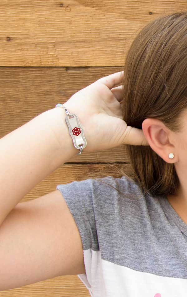 Girl with hand in her hand and wearing silver diabetes bracelet with decorative edge
