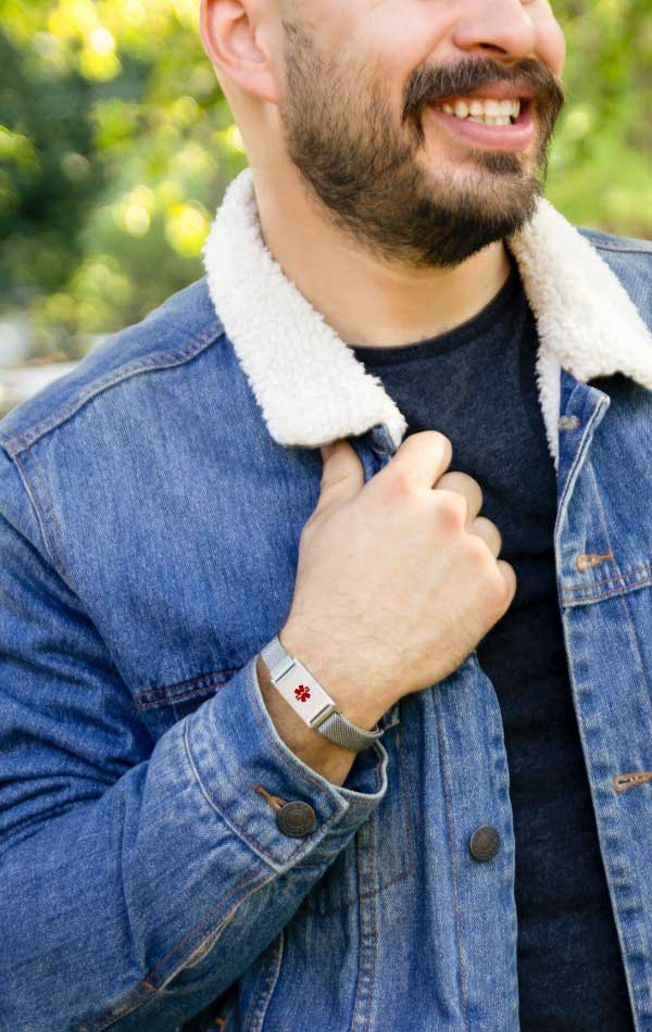 Man wearing denim jacket and holding collar while wearing silver diabetes bracelet with mesh band