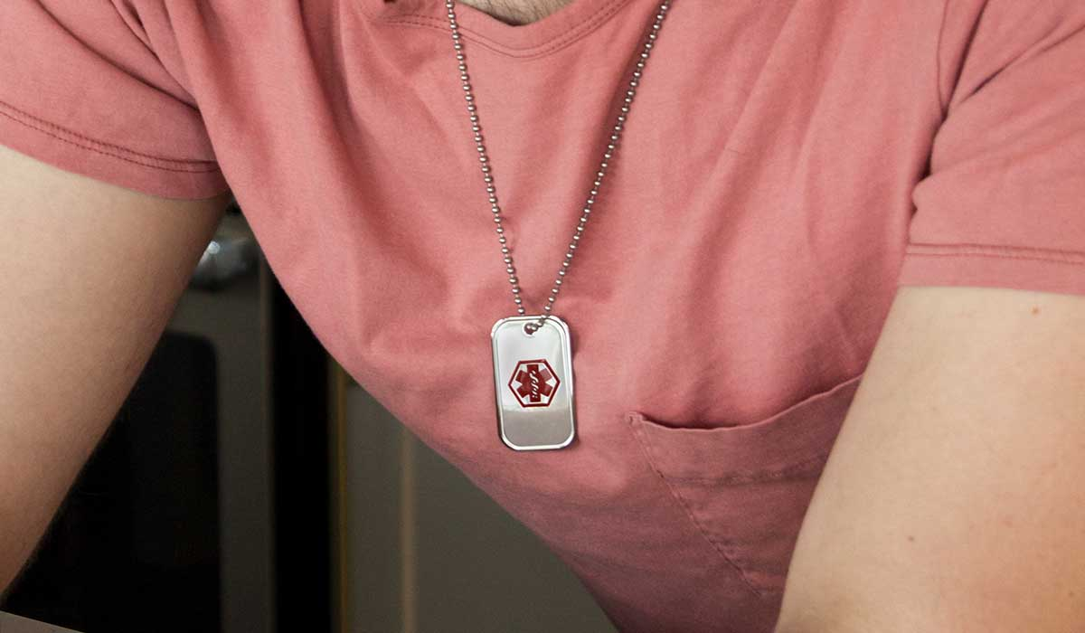 Man wearing medical alert dog tag necklace for cancer condition