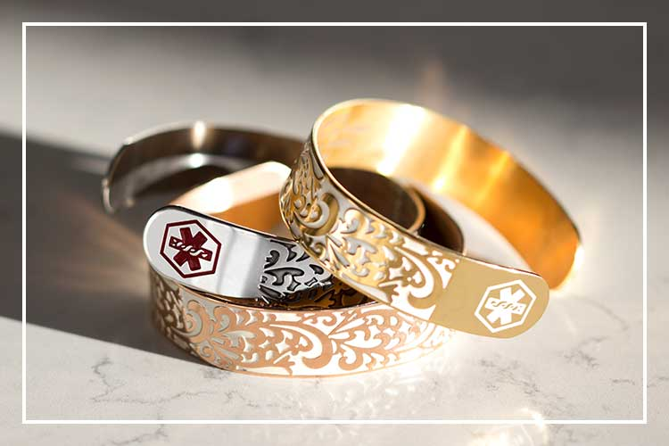 Stack of medical alert cuffs in silver, rose gold, and gold with filigree pattern