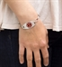Woman wearing the silver-tone Stainless Red Oval Medical ID Tag with a red caduceus in the center on an LH bracelet
