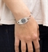 Woman wearing the silver-tone Stainless Charcoal Oval Medical ID tag with charcoal medical caduceus symbol on an LH bracelet