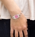 Woman wearing the silver-tone Stainless Pink Oval Medical ID Tag with pink medical caduceus symbol on an LH bracelet