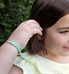 Girl wearing the Sunny Skies Medical ID Bracelet with the front of the single bank multi-color cord showing several colors