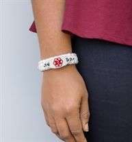 Woman wearing white Beach Day Paracord Medical ID Bracelet with oval silver tone stainless medical ID tag with red caduceus