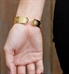 Woman wearing Golden Filigree Medical ID Cuff. Stainless yellow gold tone filigree with pearlescent finish. White caduceus