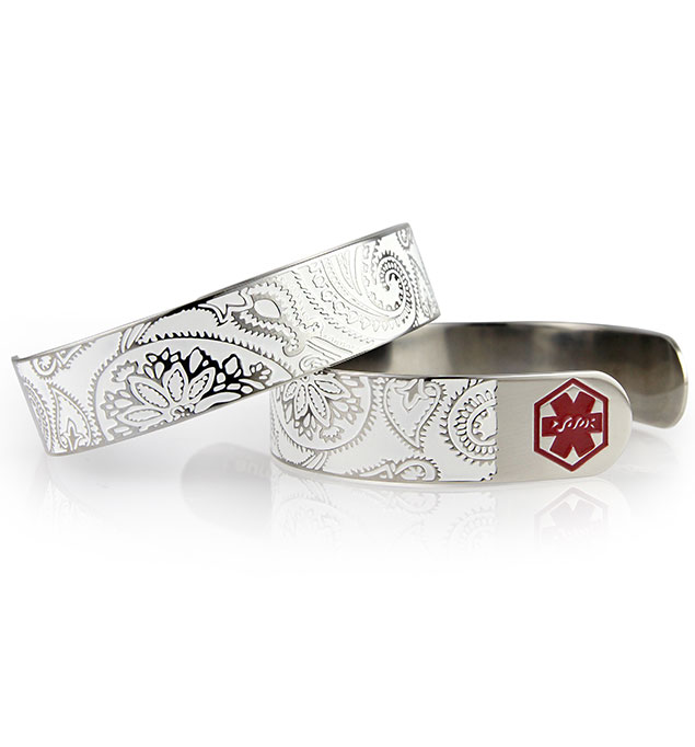 Dolly Medical ID Cuff front and back. ½ inch silver tone stainless, paisley pattern, white inlay. Red caduceus each end