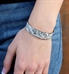 Woman wearing the Dolly Medical ID Cuff, a half-inch silver tone stainless cuff with a paisley pattern and white inlay