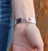 "Woman wearing Dolly Medical ID Cuff. 1/2"" silver tone stainless cuff, paisley pattern white inlay, red caduceus each end"