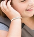 Girl wearing and showing the Rose Gold Tone La Petite Med ID tag on the Nova Medical ID Bracelet, a white band with sparkles