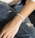 Woman wearing and showing the front of the Nova Medical ID Bracelet, a flat white leather band with white sparkles