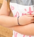 Young girl with arms crossed wearing the Prism Medical ID Bracelet, a flat leather band with multi-color sparkles