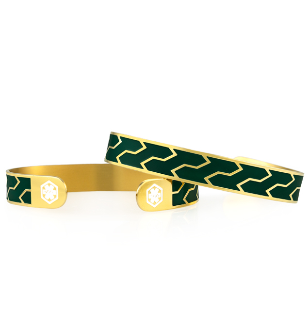 Set of two gold tone cuffs with deep green paint insets, repeating pattern, white medical symbols on each end