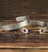 2 Sleek Mini Med ID Cuffs in Silver with smooth brushed surface both sides, red caduceus each end. Resting on wood surface