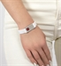 Woman wearing white ActiveWear medical alert band with silver tag and red medical caduceus