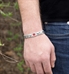 Man wearing the Roadrunner Medical ID Bracelet, a silver-tone stainless chain bracelet with an affixed tag and red caduceus