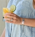 Woman wearing the silver tone stainless slip-on SmartFit Medical ID Bracelet with the La Petite medical ID tag, red caduceus